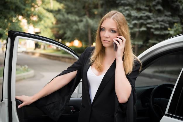 Jovem mulher está falando no telefone perto do carro.