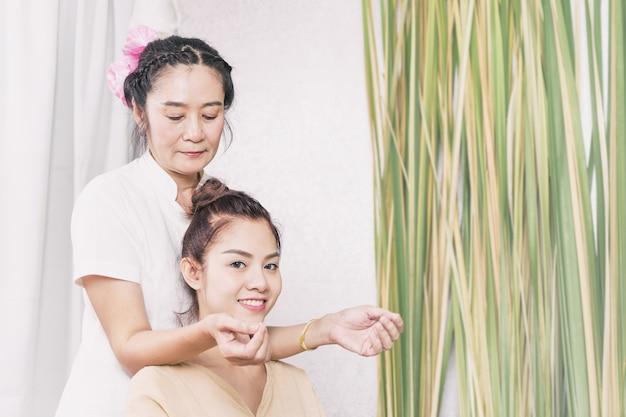 Jovem mulher está ficando ombro e pescoço massagem no spa tailandês