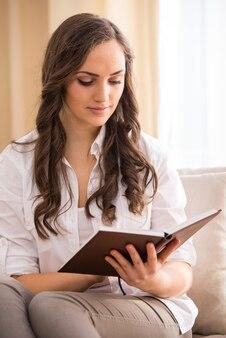 Jovem mulher está lendo um livro no sofá.