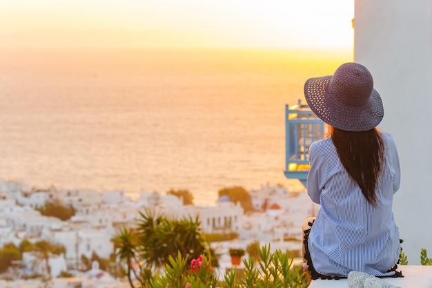 Jovem mulher está olhando o pôr do sol sobre um mar na famosa vila de míconos