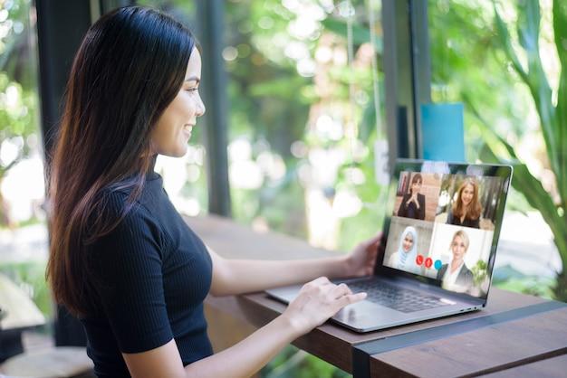 Jovem mulher está olhando para a tela do computador durante uma reunião de negócios através do aplicativo de videoconferência
