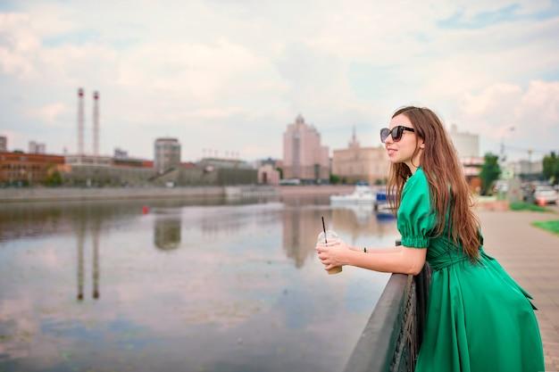 Jovem mulher está olhando para o pôr do sol sobre um rio na cidade