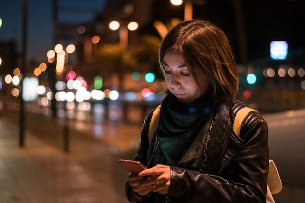 Jovem mulher está olhando seu smartphone à noite.