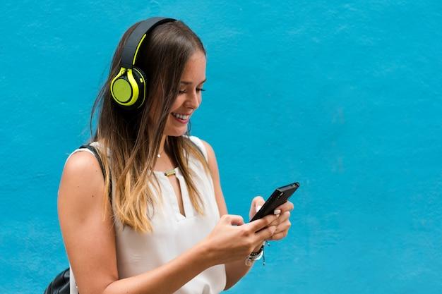 Jovem mulher está ouvindo música com seus fones de ouvido no fundo azul
