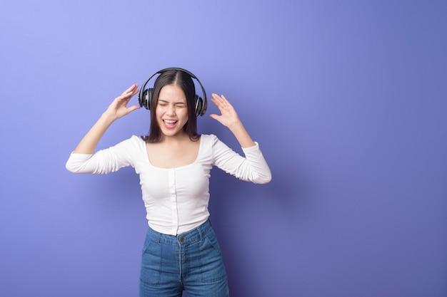 Jovem mulher está ouvindo música no fundo roxo
