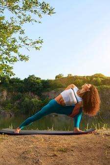 Jovem mulher está praticando ioga perto do rio