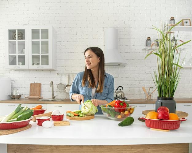 Jovem mulher está preparando uma salada na cozinha.