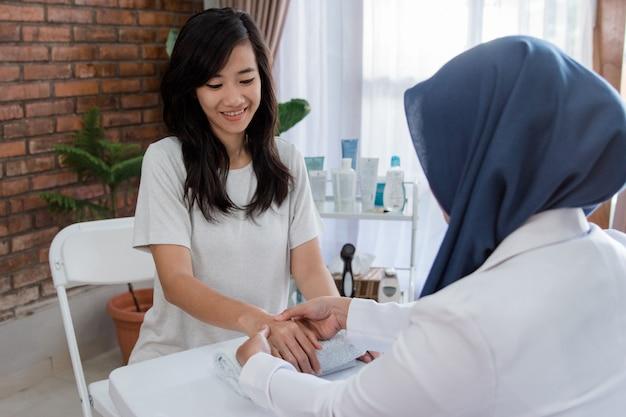 Jovem mulher está recebendo uma massagem de mão com esteticista