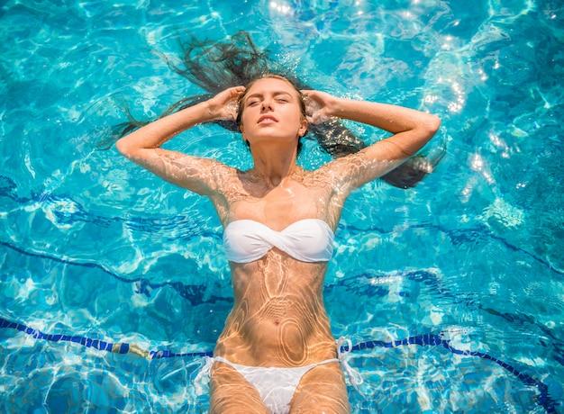 Jovem mulher está relaxando na piscina.