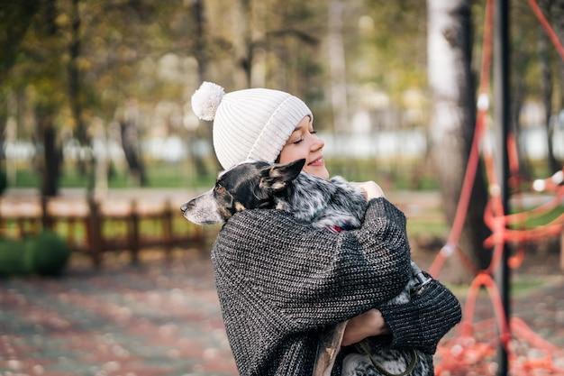 Jovem mulher está segurando um cachorro nos braços