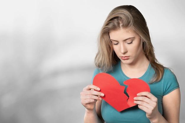 Jovem mulher está segurando um coração partido, isolado no fundo.