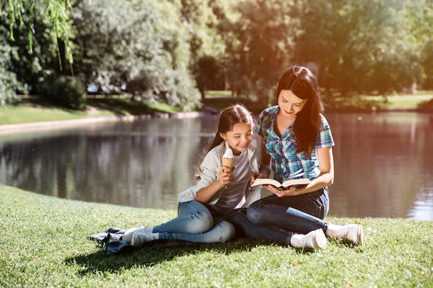 Jovem mulher está sentada junto com a filha e lendo um livro. eles estão olhando para o livro juntos. menina está inclinada para a mãe dela. ela está tomando sorvete.