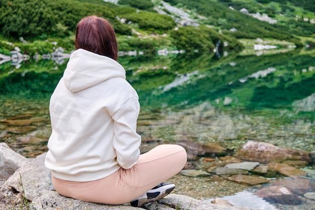 Jovem mulher está sentada na margem do lago com águas límpidas e transparentes e desfruta de uma vista com espaço de cópia. relaxamento e meditação sobre o conceito de natureza.