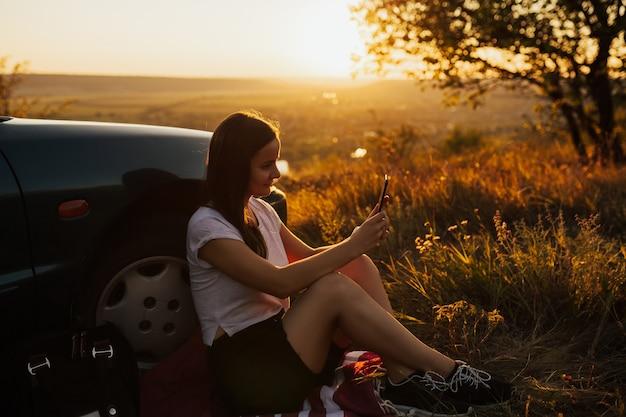 Jovem mulher está sentada perto do carro e olha para o telefone inteligente na viagem ao pôr do sol incrível.