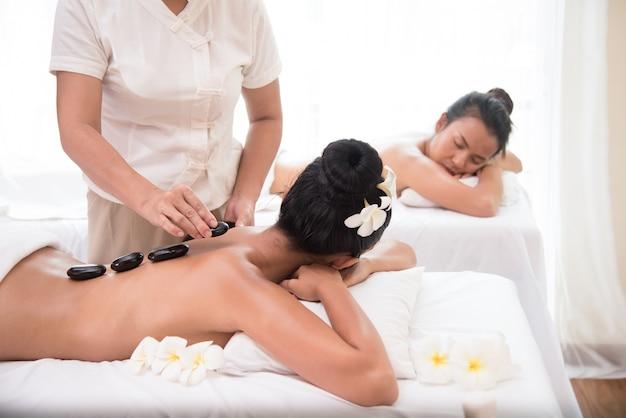 Jovem mulher está tendo massagem com pedras quentes no salão spa, saúde e conceito de cura.
