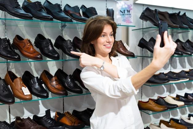 Jovem mulher está tomando selfie com botas para homens na loja e apontando para o sapato preto