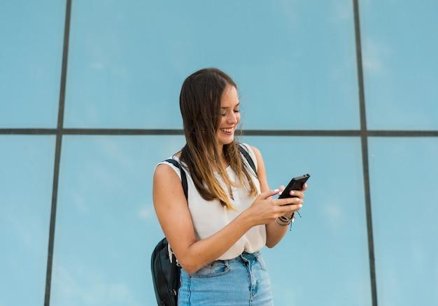 Jovem mulher está usando seu smartphone, há um espelho atrás dela