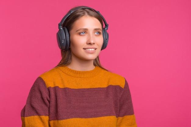 Jovem mulher está usando um par de fones de ouvido sobre fundo rosa.