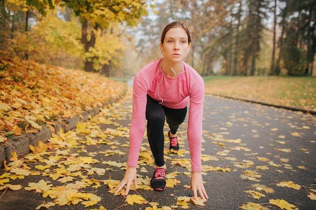 Jovem mulher estica seu corpo e estamos ansiosos. ela fica em posição e pronta para correr. mulher esbelta e bem construída, ouve música através dos fones de ouvido.