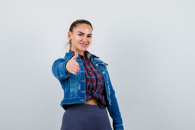 Jovem mulher esticando a mão para a frente em camisa quadriculada, jaqueta jeans e linda.