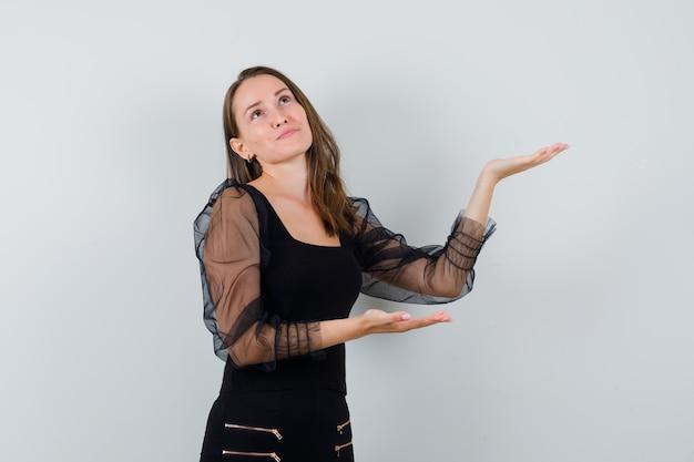 Jovem mulher esticando as mãos, apresentando algo de blusa preta e calça preta e olhando feliz, vista frontal.
