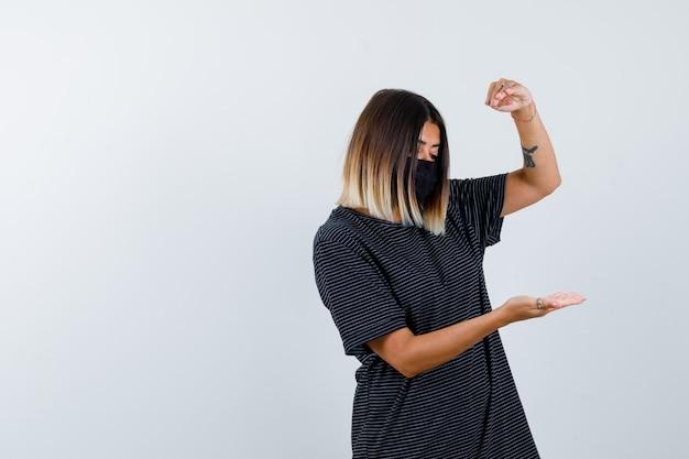 Jovem mulher esticando as mãos como segurando algo em um vestido preto, máscara preta e olhando com foco, vista frontal.