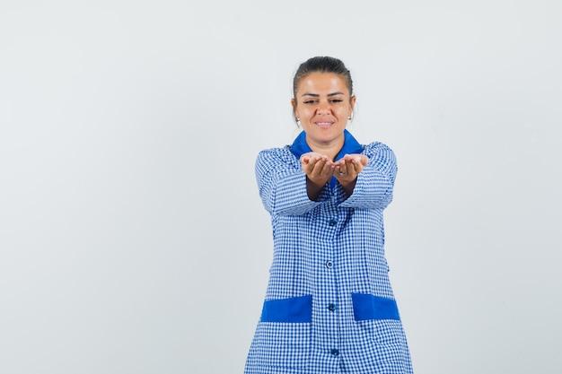 Jovem mulher esticando as mãos como um convite para entrar em uma camisa de pijama de algodão xadrez azul e parecendo amável. vista frontal.