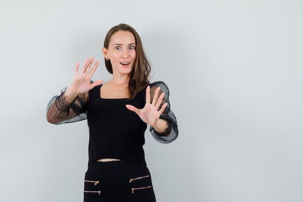 Jovem mulher esticando as mãos para parar algo em blusa preta e calça preta e parece feliz. vista frontal.
