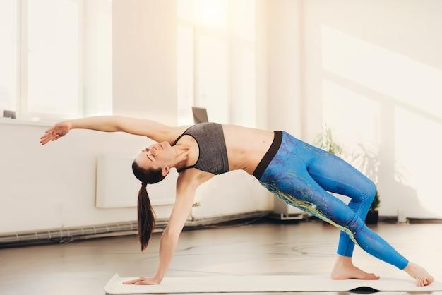 Jovem mulher esticando e fazendo exercícios de ioga no estúdio