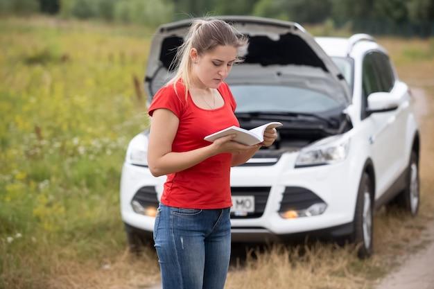 Jovem mulher estressada parada em frente a um carro quebrado lendo o manual do proprietário