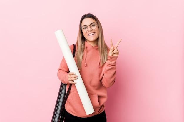Jovem mulher estudando arquitetura alegre e despreocupada, mostrando um símbolo de paz com os dedos.