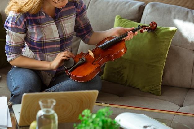 Jovem mulher estudando cursos online de música em casa.