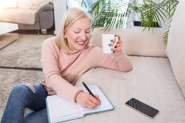 Jovem mulher estudando e tomando café, jovem estudiosa que trabalha em casa, sentada no chão na sala de estar com uma nota de classe em pastas para estudar para a universidade