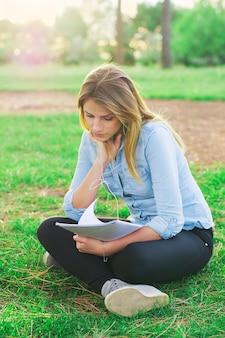 Jovem mulher estudando no parque