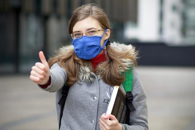 Jovem, mulher, estudante universitária ou universitária em máscara protetora no rosto e de óculos, segurando um livro, livro didático e mochila, aparecendo o polegar, como. coronavirus, covid-19, conceito de educação.