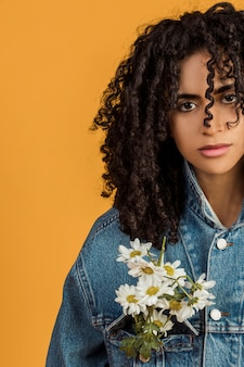Jovem mulher étnica com flores na jaqueta jeans