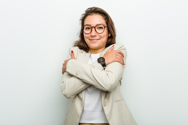 Jovem mulher europeia abraça-se, sorrindo despreocupada e feliz.