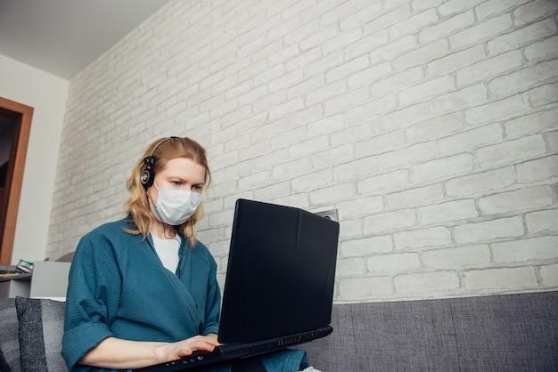 Jovem mulher européia caucasiana em máscara médica e fones de ouvido usando o laptop no sofá durante o trabalho remotamente em casa devido à pandemia de coronavírus