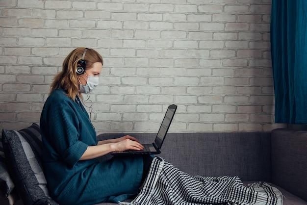 Jovem mulher europeia caucasiana usando máscara médica e manta usando o laptop no sofá durante o trabalho remotamente em casa devido a uma pandemia de coronavírus