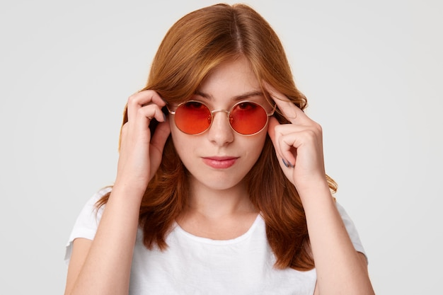 Jovem mulher européia concentrada com expressão séria, mantém as mãos nos templos, tenta se concentrar em algo, usa óculos de sol vermelhos e camiseta casual branca,