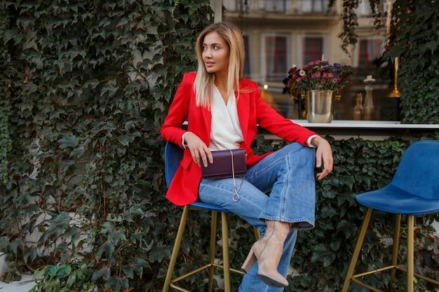 Jovem mulher europeia confiante com um sorriso sincero, posando ao ar livre no bar