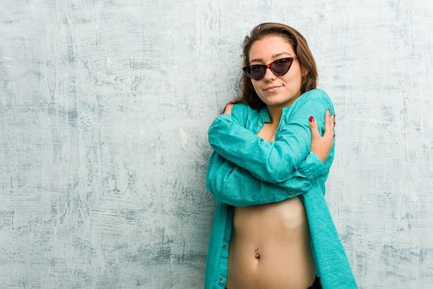 Jovem mulher europeia de biquíni se abraça, sorrindo despreocupada e feliz.