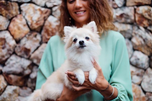 Jovem mulher europeia em vestido de verão romântico com pulseira segurando um cachorrinho fofo da pomerânia perto da vila