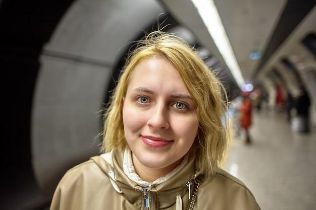 Jovem mulher europeia fica na plataforma de uma estação de metrô subterrânea, esperando o trem.