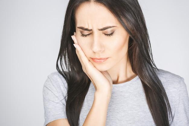 Jovem mulher europeia isolada no fundo branco, sofrendo de dor de dente severa, sentindo uma dor tão forte que pressiona os dedos na bochecha para acalmá-la, parecendo desesperada.