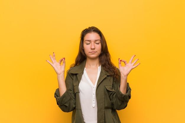 Jovem mulher europeia isolada sobre fundo amarelo relaxa após um árduo dia de trabalho, ela está realizando ioga.