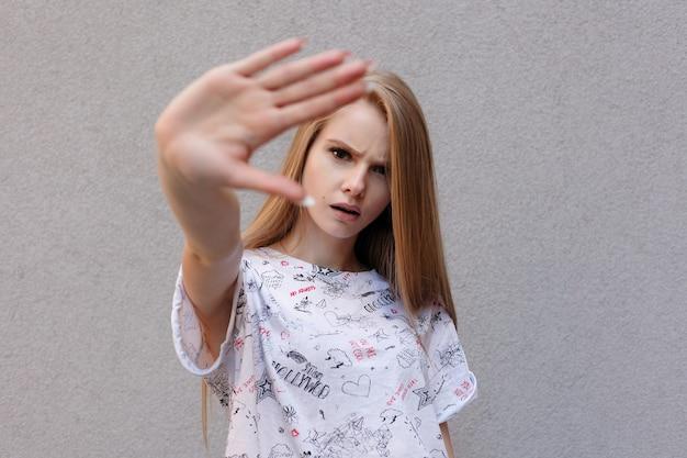 Jovem mulher europeia na moda com expressão de raiva insatisfeita, segurando a mão em gesto de parar, tentando cobrir o rosto da câmera, isolado sobre o fundo branco. é difícil ser modelo famoso