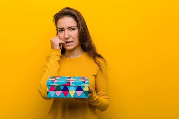 Jovem mulher europeia segurando as unhas roer um presente, nervoso e muito ansioso.