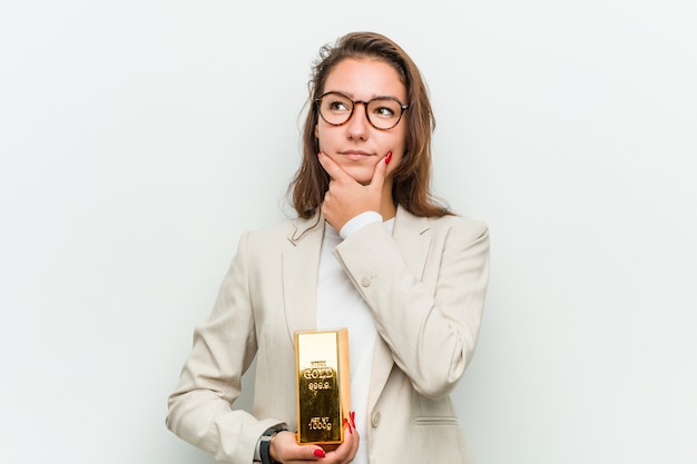 Jovem mulher europeia segurando um lingote de ouro, olhando de soslaio com expressão duvidosa e cética.