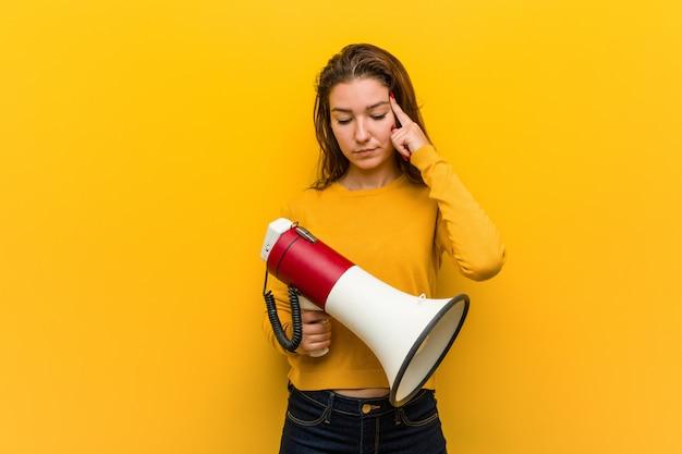 Jovem mulher europeia segurando um megafone, apontando seu templo com o dedo, pensando, focado em uma tarefa.